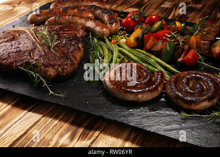 Assorted delicious grilled meat with vegetable on a barbecue with t-bone steak and sausages - Stock Photo