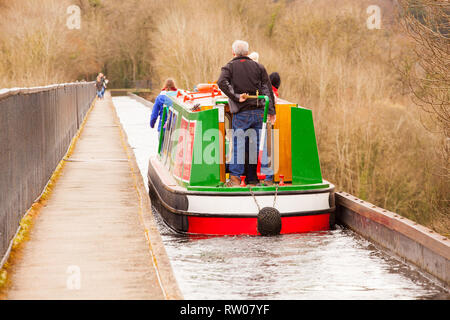 Man steering a narrow boat over the Pontcysyllte Aqueduct on the Llangollen canal  in North Wales above the river Dee built by Thomas Telford 1805 - Stock Photo