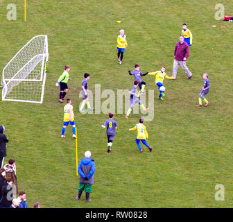 Schoolboys playing an amateur schoolboy sport football  match game - Stock Photo