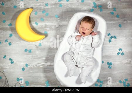 Newborn baby yawns in a special orthopedic mattress Baby cocoon, on a wooden floor, toy moon and puzzles around. Calm and healthy sleep in newborns. - Stock Photo