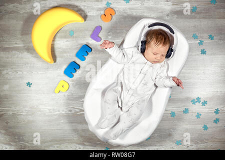 Newborn baby sleeps in a special orthopedic mattress Baby cocoon, on a wooden floor multicolored letters around. Calm and healthy sleep in newborns. - Stock Photo
