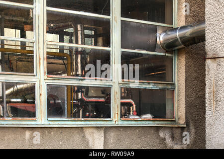 Small old heating plant windows from outside. Heat pipes covered in silver foil visible behind glass. - Stock Photo