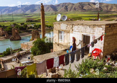 Hasankeyf, Batman province, Turkey : A woman does laundry on the rooftop of her house overlooking the Tigris river in the historical town of Hasankeyf - Stock Photo
