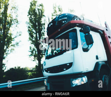 Defocused view of white truck transporting multiple cars on German highway - Stock Photo