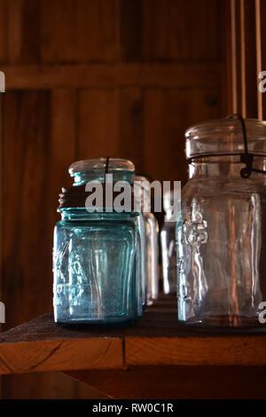 Vintage lidded glass jars on a wooden shelf with wooden slat background. Shingle Creek Pioneer Village, Kissimmee, Florida, USA - Stock Photo