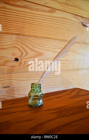 Antique glass inkwell with quill on wooden shelf with plain wooden background. Shingle Creek Pioneer Village, Kissimmee, Florida, USA. - Stock Photo