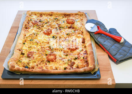 Freshly backed delicious crunchy homemade pizza with vegetables, tomato, corn, pumpkin on a rectangular metal tray and wooden table - Stock Photo
