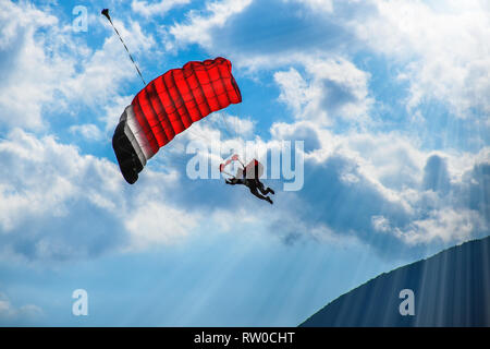 Paraglider with red parachute flying in the blue sky with white clouds on a sunny day - Stock Photo