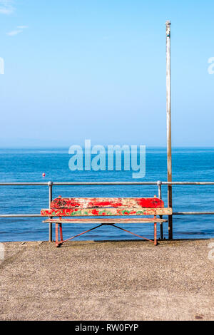 A battered red painted bench on the promenade with the sea and blue sky behind. - Stock Photo