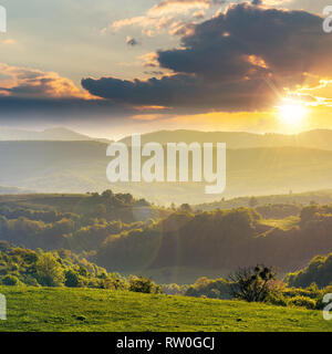 green rolling hills of romania countryside at sunset. agricultural field with green grass. mountain ridge in the distance. cloudy sky. wonderful weath - Stock Photo