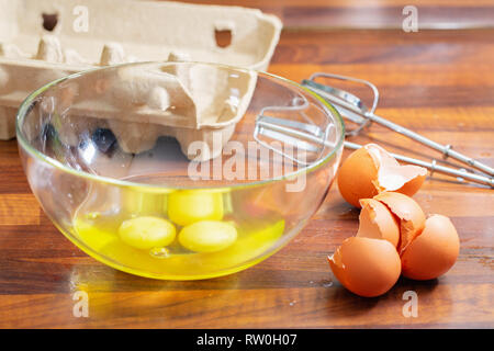 Broken raw eggs in a glass bowl and shell next - Stock Photo