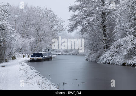 Canal boat moored on the Macclesfield Canal near Bollington in winter.  The trees and towpath are covered with snow - Stock Photo