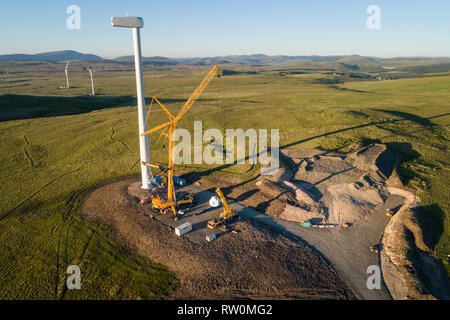 Aerial image showing construction of wind turbines using cranes at Andershaw Wind Farm near Douglas in South Lanarkshire, Southern Scotland. - Stock Photo