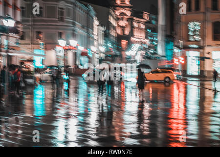 City street in rainy night, Abstract bright blurred background with unidentified people. Vivid illumination, reflection in wet pavement of shop - Stock Photo