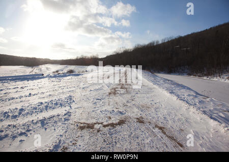 A dirt path covered in snow with a river on one side on a beautiful day - Stock Photo