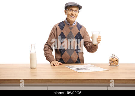 Elderly man holding a glass of milk and standing behind a wooden counter isolated on white background - Stock Photo