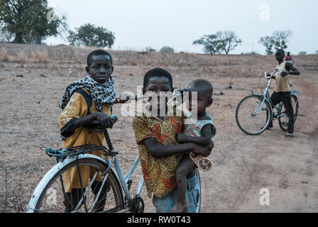 A beautiful photo of cheerful and happy Ghanaian children posing with their bicycles when they are heading back home after long days work. - Stock Photo