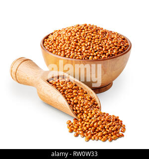 Millet in shells in a wooden bowl with a scoop isolated on white - Stock Photo