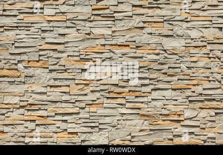 Tiled stone wall made of rectangular blocks, sun shining from top. - Stock Photo