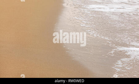 Wet sand on beach, remains of water with white foam showing on the right, overcast day. Abstract sea background. - Stock Photo