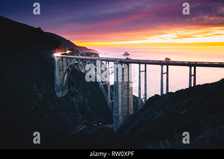 Bixby Creek Bridge with Colorful Sunset and Car Light Trails, Big Sur, CA - Stock Photo