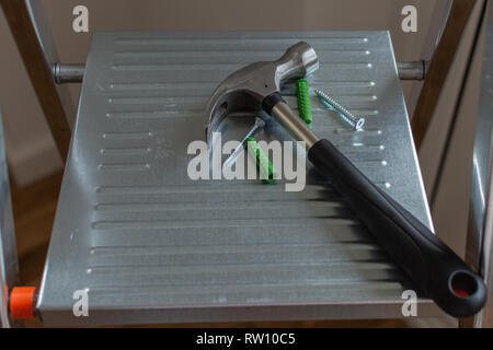 Hammer with screws and wall plugs lie on the stepladder, repairs in the house - Stock Photo