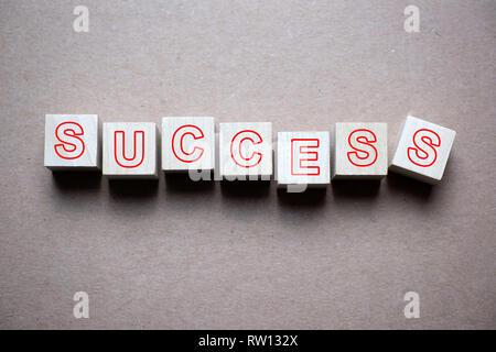 Success word written on wood cube - Stock Photo