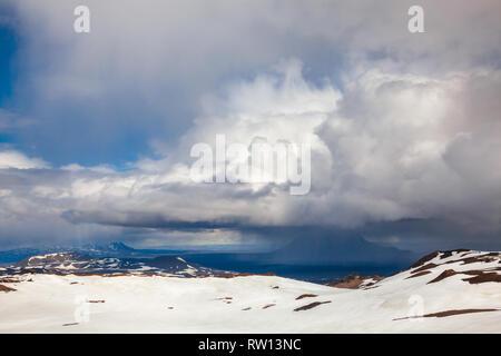 Stormy clouds raining over the Herdubreid tuya mountain in Ódáðahraun lava field, Highlands of Iceland, Scandinavia, as viewed from snowed Askja volca - Stock Photo