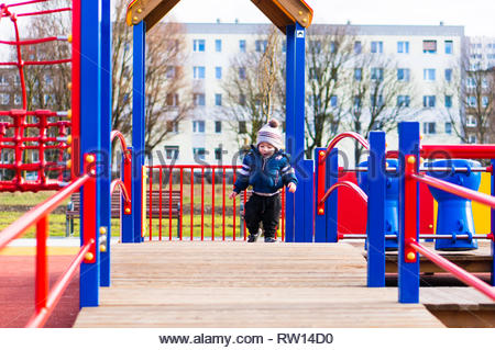 Poznan, Poland - February 24, 2019: Toddler boy in winter clothes walking on a wooden platform of a climb equipment on a playground in the Rataje park - Stock Photo