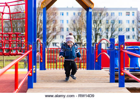 Poznan, Poland - February 24, 2019: Young toddler boy in warm clothes running on a wooden platform with red barriers of a equipment in a playground on - Stock Photo