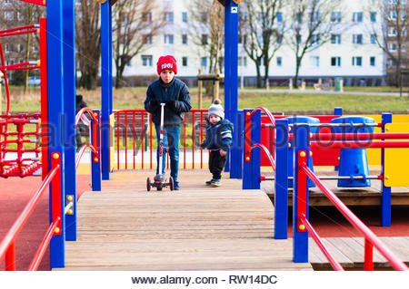 Poznan, Poland - February 24, 2019: Young boy riding a child scooter on a wooden platform of a equipment on a playground. - Stock Photo