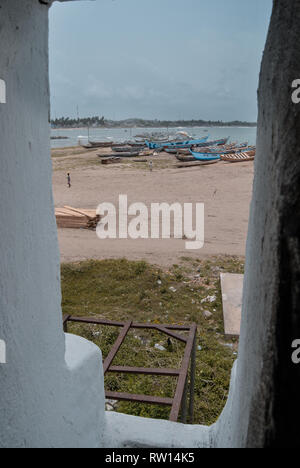 A view to the landscape (sandy beach and old wooden boats) surrounding the old Elmina slave castle in Elmina, Ghana, West Africa - Stock Photo