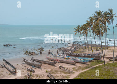 A landscape photo of the beautiful tropical coast and sandy beach at Elmina, Ghana. Old traditional wooden fishing boats are stored at the beach. - Stock Photo