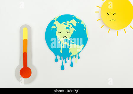 paper cut sun and melting earth with sad faces expression, and thermometer with high temperature indication on scale on grey background, global warmin - Stock Photo