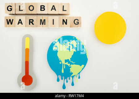 paper cut melting earth and sun, thermometer with high temperature indication on scale, and wooden cubes with 'global warming' lettering on grey backg - Stock Photo