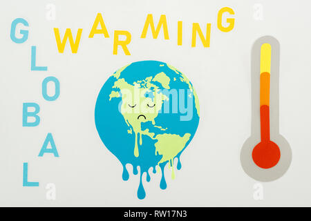 paper cut melting globe with sad face expression, 'global warming' lettering, and thermometer with high temperature indication on scale on grey backgr - Stock Photo
