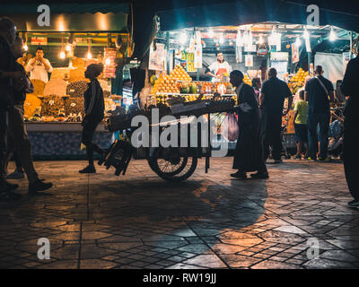 MARRAKESH, MOROCCO - March 27, 2018: Medina of Marrakesh at Djemaa el Fna square at night, crowded with tourists - Stock Photo