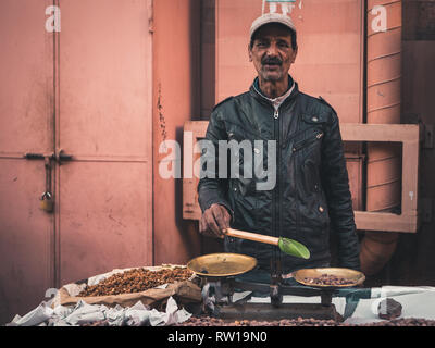 MARRAKESH, MOROCCO - March 27, 2018: portrait of a male vendor on the street selling nuts - Stock Photo