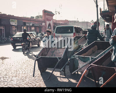 MARRAKESH, MOROCCO - March 27, 2018: busy street in Marrakesh with various trolleys standing aside - Stock Photo