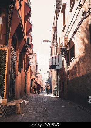 MARRAKESH, MOROCCO - March 27, 2018: Cobblestone Street of the old medina in Marrakesh, Morocco with motorbikes on the side - Stock Photo