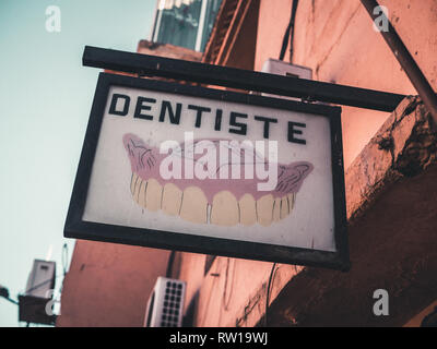 MARRAKESH, MOROCCO - March 27, 2018: Dentist's practice sign in the old medina in Marrakesh, Morocco. - Stock Photo