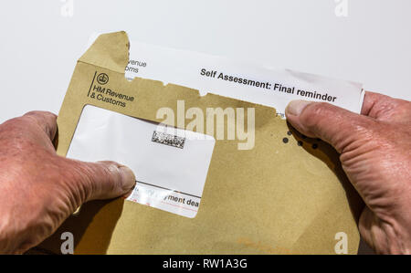 Opening a final reminder letter from HM Revenue & Customs  for paying tax. - Stock Photo