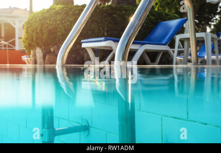 Partially underwater photo, steel handrails at entry to swimming pool, backlight sun shining in background. Vacation / relax image. - Stock Photo