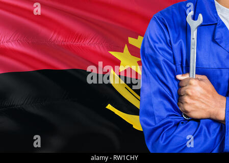 Angolan Mechanic in blue uniform is holding wrench against waving Angola flag background. Crossed arms technician. - Stock Photo