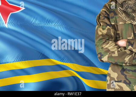 Crossed arms soldier with national waving flag on background - Aruba Military theme. - Stock Photo