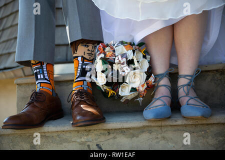Bride and groom standing together showing shoes, socks, and flower bouquet on wedding day - Stock Photo