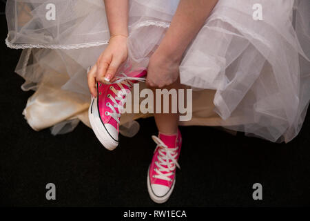 Bride putting on and lacing pink sneakers on feet - Stock Photo