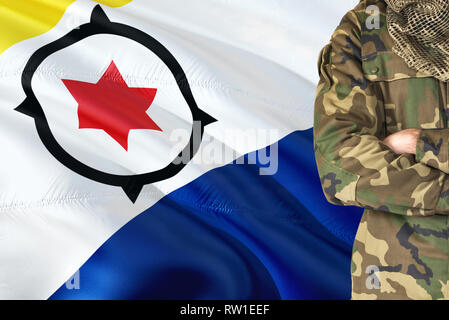 Crossed arms soldier with national waving flag on background - Bonaire Military theme. - Stock Photo
