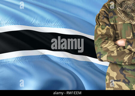 Crossed arms soldier with national waving flag on background - Botswana Military theme. - Stock Photo