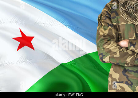 Crossed arms soldier with national waving flag on background - Djibouti Military theme. - Stock Photo